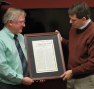 Senator Mark Begich [D-Alaska], right, presents Jon E. Zufelt, Ph.D., P.E., M.ASCE with a copy of Congressional Record, which recognizes his 30 years of service at the Engineer Research and Development Center's Cold Regions Research and Engineering Laboratory with the U.S. Army Corps of Engineers. Photo Credit: Jon E. Zufelt