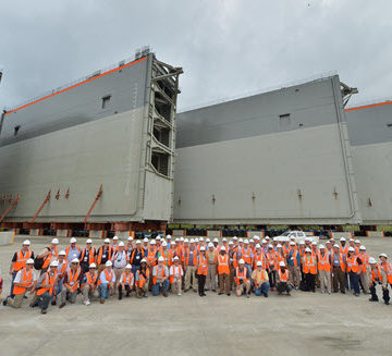 A group of attendees at ASCE's Global Engineering Conference in Panama tour the Atlantic Third Lane Bridge and Lock canal expansion project, gathering at a temporary dock where new lock gates await installation. Photo Credit: Panama Canal Authority