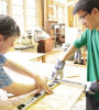 Brendan Sullivan, left, and Steven Lin measure and cut pieces of wood for the Brooklyn Technical High School ASCE Club's hydroelectric dam project.
