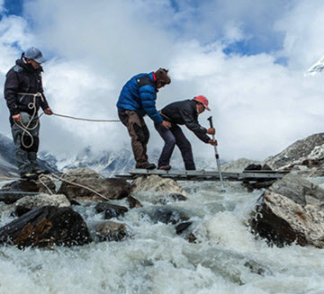 The research team inches out along a precarious perch to measure discharge waters at Imja Lake. Photo: Daniel Byers