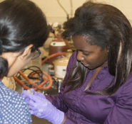 Ange Therese Akono works with a student.