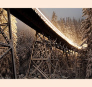 "Honan's photo of the BNSF Railway's Foss River Bridge in Skykomish, WA,  that earned grand-prize honors in Trains Magazine's 2009 Photo Contest. ""I had gone up there in the midst of a Cascade Range blizzard specifically to photograph this bridge at night, but I couldn't have imagined that in mid-storm the clouds would tear apart to let a 3/4-full moon shine onto the scene,"" Honan said. ""The timely passage of an eastbound train provided me the opportunity to capture this surreal scene that seems more painting than photograph."""