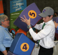 A student takes part in a bridge-building exercise with an ASCE staffer's help at the USA Science & Engineering Festival.