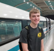 Nathan stands in front of the Shanghai Maglev train.