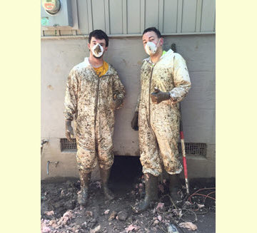 Marshall student Austin Page, S.M.ASCE, and Marshall professor Andrew Nichols, Ph.D., P.E., M.ASCE, don special suits to clean up mud and debris left over from the June floods in West Virginia.