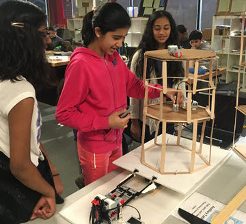 Students in the ASCE Civil Engineering Club at BASIS Independent Silicon Valley School build a structure out of popsicle sticks.