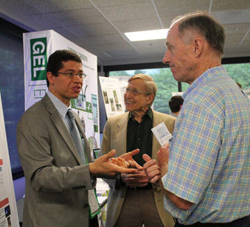 Innovation Contest winners Samer Dessouky, left, and Jim Stewart, center, talk with ILC member and Disney Imagineering VP Mike McCullough.