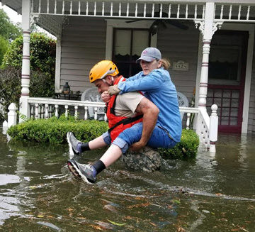 A Texas National Guardsman carries a resident from her flooded home. PHOTO: U.S. Dept. of Defense