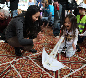 Kids test paper towers against winds from a box fan in the Windy City Tower activity.